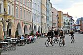 Four cyclists cycling over Max-Joseph-Place, Rosenheim, Bavaria, Germany