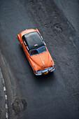 Orange vintage American car taxi on Malecon sea wall, City of Havana, Havana, Cuba