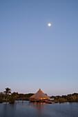 Moon above restaurant at Villa Guama hotel on the shores of Laguna del Tesoro (Treasure Lake) at dusk, Guama, Matanzas, Cuba