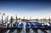 Venetian gondolas resting in front of St Mark's Squares, wooden boat across the Grand Canal and San Giorgio Maggiore island in background, Venice, Veneto, Italy