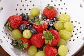 strawberries blueberries grapes in a colander being washed before eating