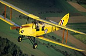 Above, Aerial, Aeroplane, Aircraft, Airplane, Biplane, British, De havilland, Dh-82, English, Flying, Historic, In air, In flight, Old, Overview, Plane, Tiger moth, Trainer, Vintage, Yellow, YA1-1046788, agefotostock