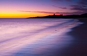 England, Northumberland, Embleton Bay A colourful display of pre-dawn colours relected upon the wet sands of Embleton Bay, overlooked by the dramatic ruins of Dunstanburgh Castle