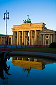 Reflection of the Brandenburg Gate Berlin Germany In Fountain Water bathed in a golden light The Brandenburg Gate German: Brandenburger Tor is a former city gate and one of the main symbols of Berlin and Germany