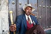 Man wearing a 1930 s fashion style suit simulating the smoking of a cigar, Havana Cuba