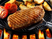 Sirloin beef steaks, tomatoes & chips being pan fried on a bbq