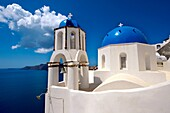 Oia, Ia Santorini - Blue domed Byzantine Orthodax churches, - Greek Cyclades islands.