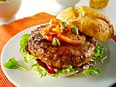 Organic beef burger with tomato relish and salad in a bun