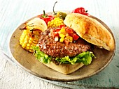 BBQ beef burger in a chabatta roll with salsa & BBQ vegetables on a rustic plate