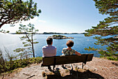 Older couple sitting on a bench, looking out to sea, coast at Mandal, Vest-Agder, South of Norway, Scandinavia, Europe