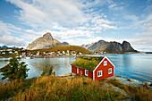 Rotes Holzhaus bei Reine, Blick auf das Meer, Landschaft auf den Lofoten, Herbst, Moskenesoy, Norwegen, Skandinavien, Europa