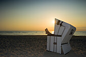 Woman relaxing in roofed wicker beach chair in sunset, Westerland, Sylt, Schleswig-Holstein, Germany