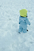 Toddler girl walking in snow, dressed in winter clothing and ski helmet, rear view