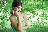 Young woman holding up apple outdoors, smiling at camera