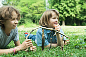 Two girls lying on grass, holding sticks, smiling, one with Down's Syndrome