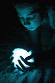 Female in the dark holding glowing sphere, looking down, close-up