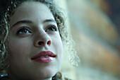 Teenage girl smiling, looking up, portrait