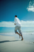 Man running at the beach, rear view, defocused