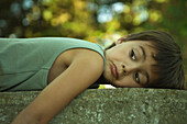 Little boy lying on stomach outdoors, frowning, looking away