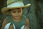 Little boy wearing straw hat, looking down, close-up