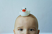Baby with rubber duck on his head, looking at camera, portrait, cropped