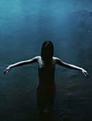 Woman standing in dark with arms out, lit from above