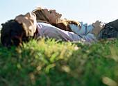 Young couple lying together in grass, smiling
