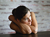 Young woman leaning on table, looking away