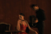 Man standing next to seated woman, playing accordion, woman looking away, defocused