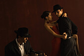 Couple tango dancing together, man playing accordion in foreground