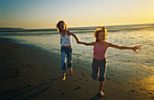 Two girls running hand in hand on beach, smiling