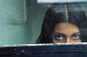 Mysterious woman peeking over ledge to look through window at camera