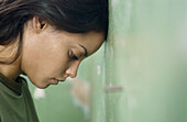 Young woman pressing her head against a wall, profile