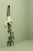 Man doing headstand on top of tall stack of chairs