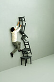 Man climbing precariously stacked chairs