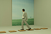 Businessman walking on footpath, looking over shoulder at rural scene