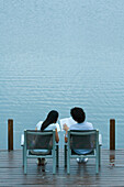 Couple sitting side by side on dock, reading books, rear view