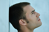 Man leaning head against wall, looking up, profile