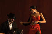 Couple tango dancing, man playing accordion in foreground