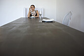 Woman sitting alone at table set for two, holding head