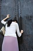 Woman standing beside closed door with head down, hand on door