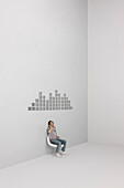 Man singing along with music playing on MP3 player, CD cases arranged in pattern on wall