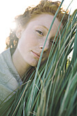 Woman with face pressed against tall grass looking at camera