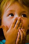 Child covering mouth with hands looking up expectantly