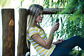 Young woman leaning against wooden railing, text messaging with cell phone