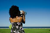 Young woman looking at sea through pay binoculars