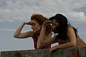 Two young women outdoors looking at view