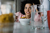 Young woman daydreaming at breakfast table