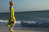 Woman in sundress walking on beach, looking at sea