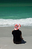 Woman sitting on beach looking at sea, rear view